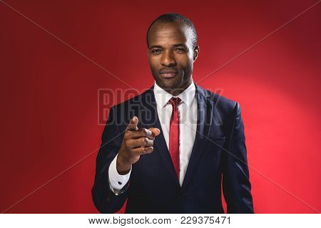 Hey You. Waist-up Portrait Of Serious Young African Manager Is Pointing You While Standing. Isolated