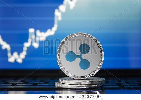 Ripple (xrp) Cryptocurrency; Silver Ripple Coin On The Background Of The Chart