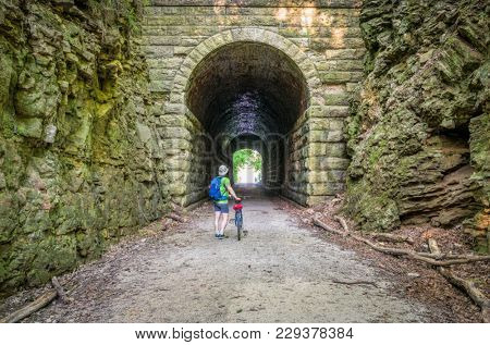 a male cyclist at MKT tunnel  on Katy Trail near Rocheport, Missouri. The Katy Trail is 237 mile bike trail stretching across most of the state of Missouri converted from an old railroad.