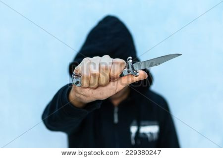 A Young Man In A Hoodie Holding A Knife Symbolizing Youth Crime. Crime Concept. The Threat Of A Cold