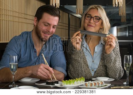 Young couple in a sushi restaurant drinking champagne.