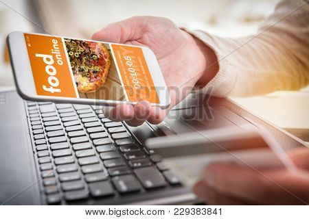 Ordering food online. Smartphone in hand and credit card in other. Concept of ordering food in office or workplace.