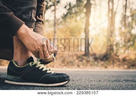 Close-up Hands Of Man Tying Shoelace During Running On The Road For Health, Color Of Vintage Tone Se