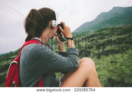 Young Woman With Backpack And Headphones Taking Photo Of Volcano In The Wild, Intentional Pale Color