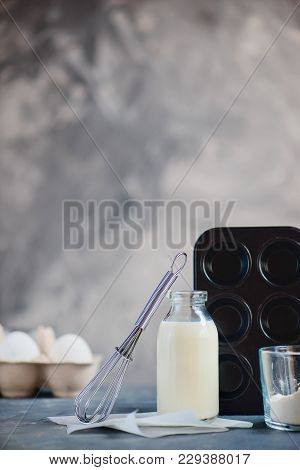 Cooking Concept With Baking Tools And Ingredients. Flour, A Muffin Tin, Whisk, A Bottle Of Milk And