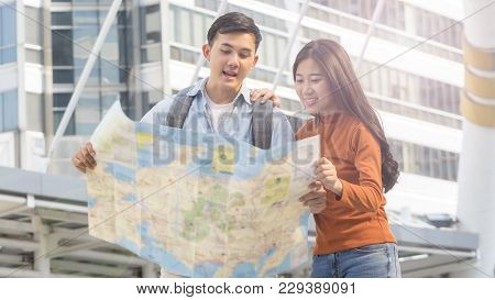Traveler Couple People Use Generic Local Map And Talk At Urban City. Honeymoon Trip, Holiday Vacatio