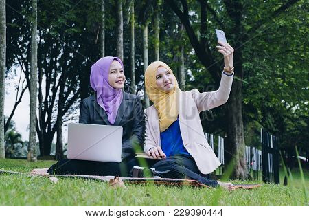 Happy Professional Muslimah Having Fun, Spend Time Together And Making Selfie In The City Park
