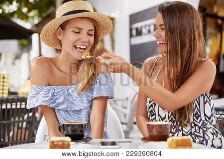 Pretty Young Woman Feed Her Lovely Girlfriend With Piece Of Delicious Cake, Have Fun Together And Dr