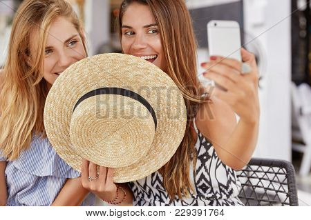 Horizontal Shot Of Attractive Beautiful Women Hide Behind Straw Hat, Make Selfie With Selphone, Shar