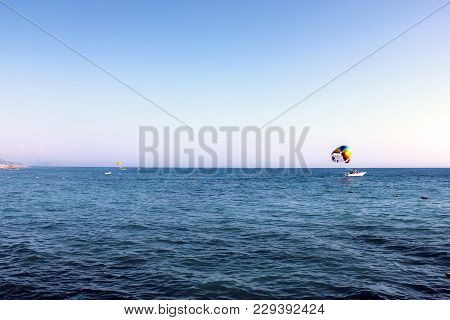 Blue Mediterranean Sea. People Fly By Parachute In The Blue Sky Over The Sea In Clear Weather, A Hol