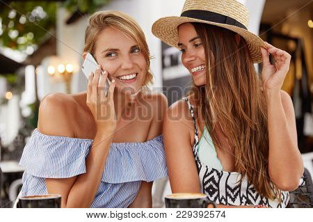 Beautiful Woman Wears Fashionable Blouse, Has Telephone Conversation With Someone While Sits Near He