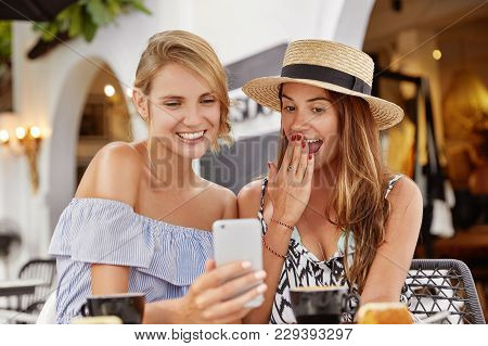 Wow, It`s Amazing! Beautiful Smiling Women Looks With Surpised And Joyful Expression In Cell Phone,
