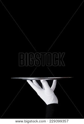 Servant Wearing White Glove Holds Stainless Steel Tray On Black Background