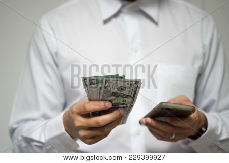 Happy Businessman Using Mobile Payments And Mobile Banking. Man Holding Us Dollar Money And Smartpho