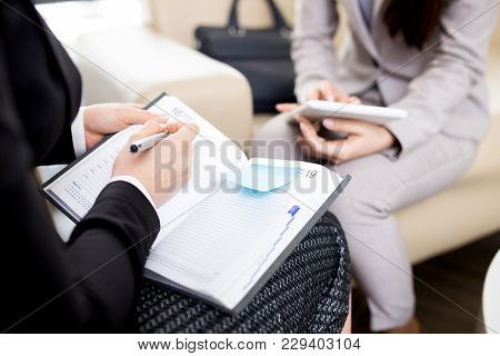 Close-up Shot Of Unrecognizable Businesswoman Sitting Opposite Her Colleague And Taking Notes While