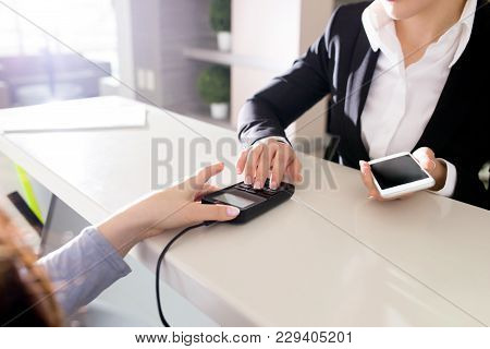 Female Customer Standing At Shop Counter And Paying For Her Purchase With Nfc Technology, Close-up S