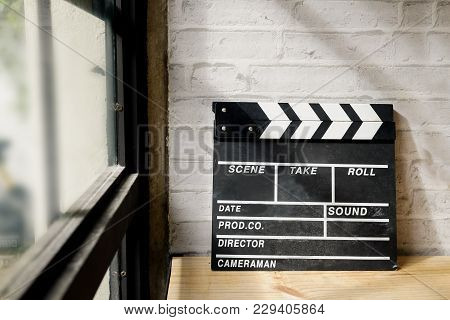 Movie Clapper On Wood Desk With Windows Light.