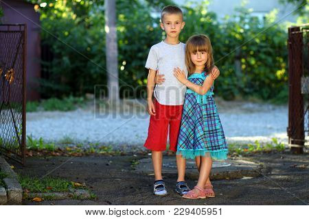 Two Little Children Brother And Sister Together. Girl In Dress Hugging Boy. Family Relations Concept