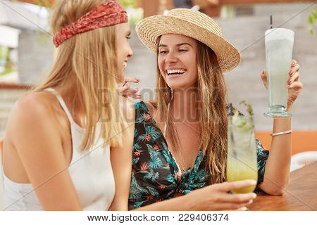 Positive Females Rest Together At Cafeteria, Drink Refreshing Cocktails, Look Positively At Each Oth