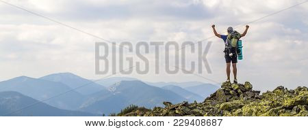 Man On Peak Of Mountain. Emotional Scene. Young Man With Backpack Standing With Raised Hands On Top