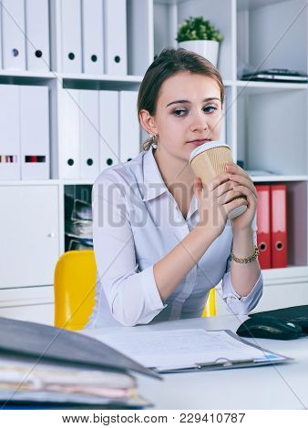 Tired And Exhausted Woman Looks At The Mountain Of Documents Holding A Paper Glass With Coffee In Ha