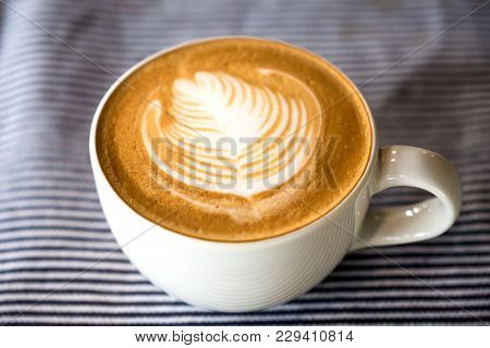 Closeup Image Of A Cup Of Hot Latte Coffee With Latte Art On Tablecloth