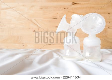 Bottles Of Automatic Breast Pump With Fresh Mother Breast Milk For Baby On White Bed Sheet And Woode