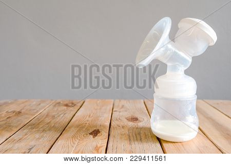 Bottle Of Automatic Pumping Breast Milk With Some Mother Milk For Baby On Wooden Table With Clipping