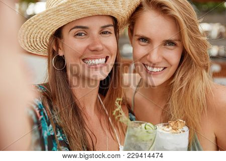 Lovely Cheerful Females With Broad Smiles, Pose For Selfie, Drink Cold Refreshing Cocktails. Relaxed
