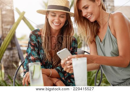 Cheerful Adorable Females Spends Free Time, Drink Cocktail And Look Something At Cell Phone, Connect