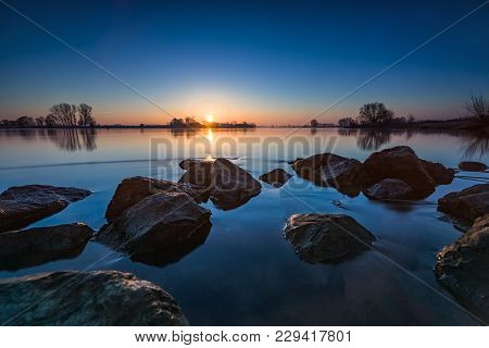 Sunrise Over The Flowing River Ijssel With Rocks And View Over The Rivers Delta Of The Netherlands.
