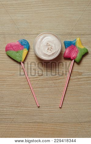 A Peach Jar Of Body Lotion Displayed With A Star Shape Lollipop And A Heart Shape Lollipop