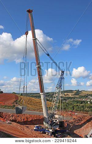 Crane Lifting A Concrete Bridge Beam On A Road Construction Site