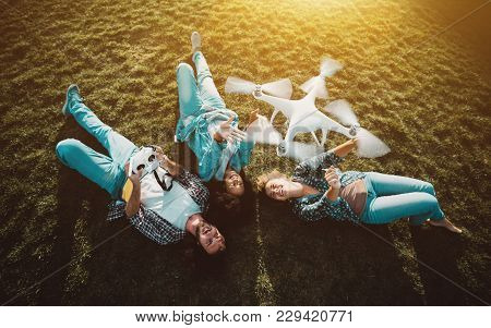 Group Of Three Happy People: Two Girls Of Different Races And One Guy Are Laying On The Meadow And P
