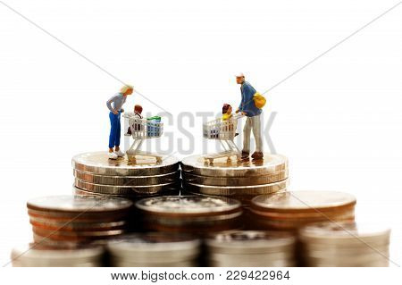 Miniature People:  Family And Children With Shopping  Cart On  Coins Stack. Concept Of Tourism, Shop