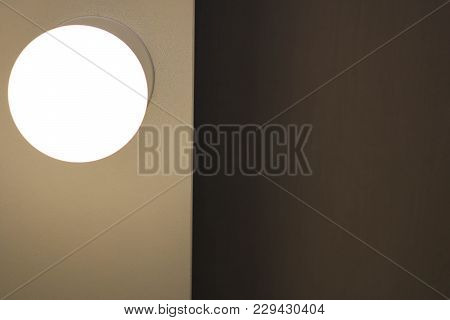 A Bright Glowing Matte White Burning Round Light Bulb On The Left And A Dark Space On The Right Clos