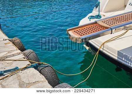 Sea Pier With Hanging Tires And Moored Yacht