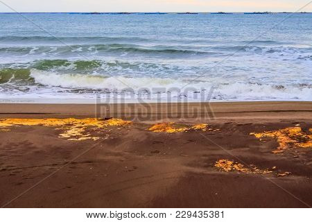 Waves Bathing The Ocher Sand Of A Beach At Sunset With Yellow Rocks
