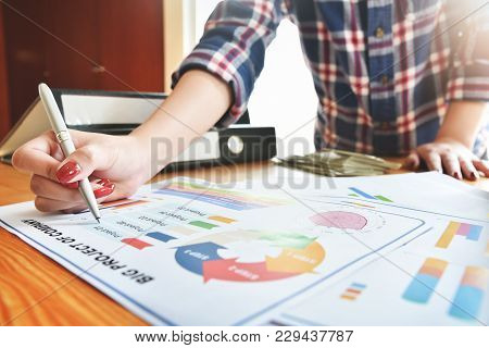 Creative Designer Hand Is Pointing On Chart Or Graph Documents With A Pen At Meeting. Marketing. Sol