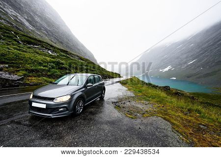 Grey Modern Car Is Parking Next To A Rural Road In A Valley Surrounded By A Fjord And Snow Covered M