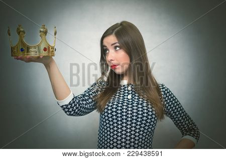 Woman Is Holding In Hands A Golden Crown Looks On It And Is Thinking. Winner. Authority.