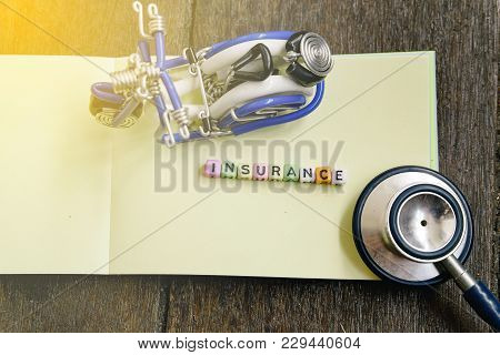 Conceptual Image With Insurance Word Block On Note Pad With Light Effect.handcrafted Souvenir And St