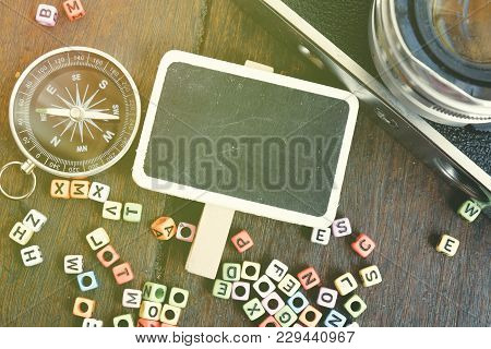 Top View Flat Lay Blank Signage,compass And Vintage Camera On Wooden Table With Alphabetical Block