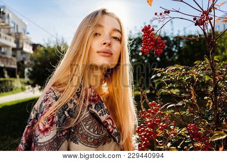 Lovely Young Long-haired Blond Girl With A Handkerchief On Her Shoulders Walking Around The Garden I