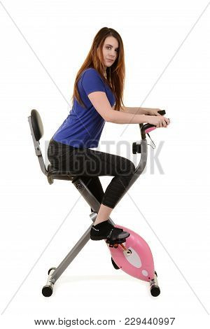 Young Woman Riding An Exercise Bike On White