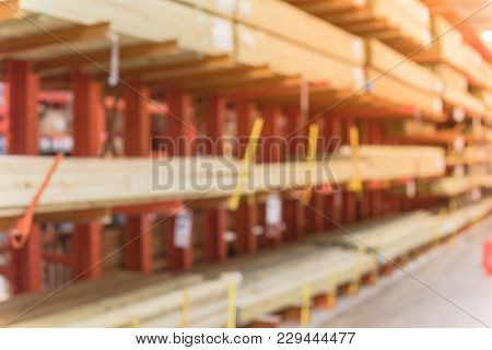 Blurred close up lumber wholesale yard at hardware store in America. Rack of fresh mill/cut wood timber in warehouse, pegboard, plywood, osb paneling, mdf. Industrial background poster
