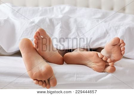 Female`s And Male`s Bare Feet Have Rest Under White Blanket, Recreat Together, Feels Relaxation. Unr