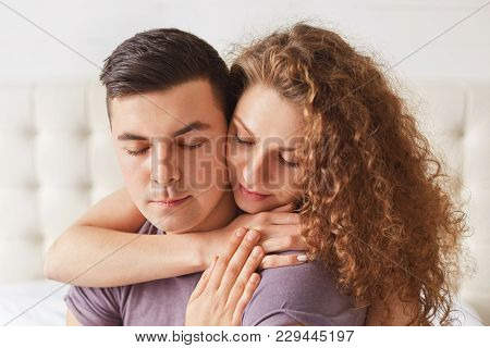Close Up Shot Of Delighted Couple Enjoy Togetherness. Lovely Young Woman With Curly Hair Embraces He