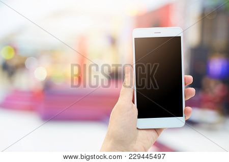 Woman`s Hands Holds Modern Electronic Gadget. Unrecognizable Female With White Mobile Phone And Blan