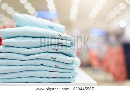 Folded Clothes In Shopping Centre. Neatly Piled Sweaters In Clothes Store. Pile Of Clothes In Modern